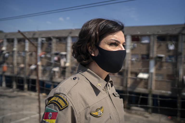 mulher de farda da PM de máscara em presídio