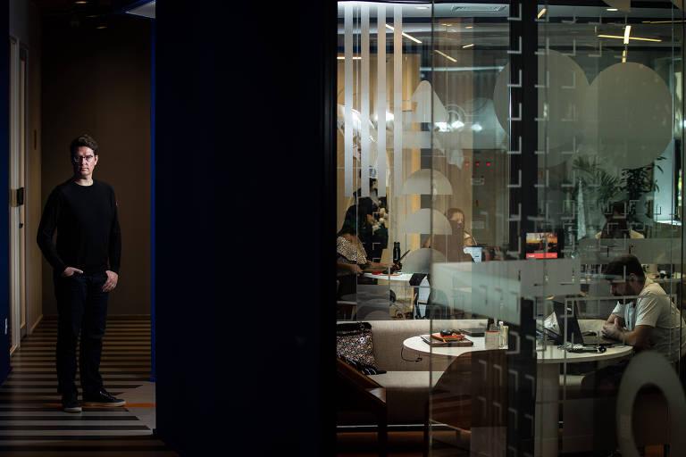 Mate Pencz à esquerda, de pé; à direita, atrás de um vidro, funcionários trabalham no escritório da Loft