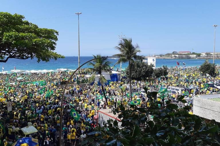 Uma multidão de pessoas vestidas de verde e amarelo com algumas palmeiras no meio e o mar ao fundo