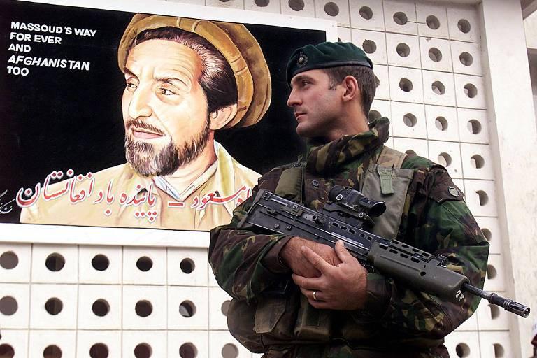 Soldado de boina e roupa verde segura rifle em frente ao peito, tendo ao fundo um retrato de um homem barbado