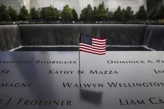 An American flag is seen in the plaque of names on the edge of the South Pool of the 9/11 Memorial  in New York