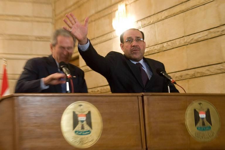 O então premiê do Iraque, Nuri al-Maliki, tenta proteger o então presidente dos EUA, George W. Bush, de sapatos atirados por um jornalista iraquiano durante entrevista coletiva em Bagdá