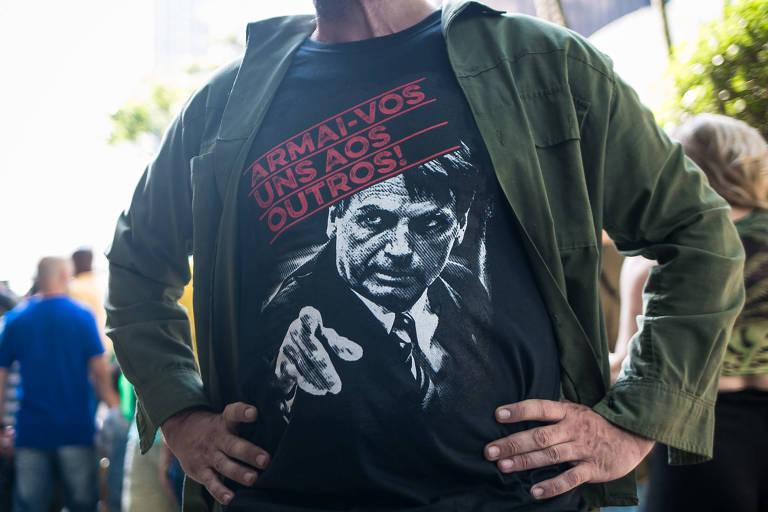 """homem veste camiseta com rosto de bolsonaro e onde se lê """"armai-vos uns aos outros"""""""