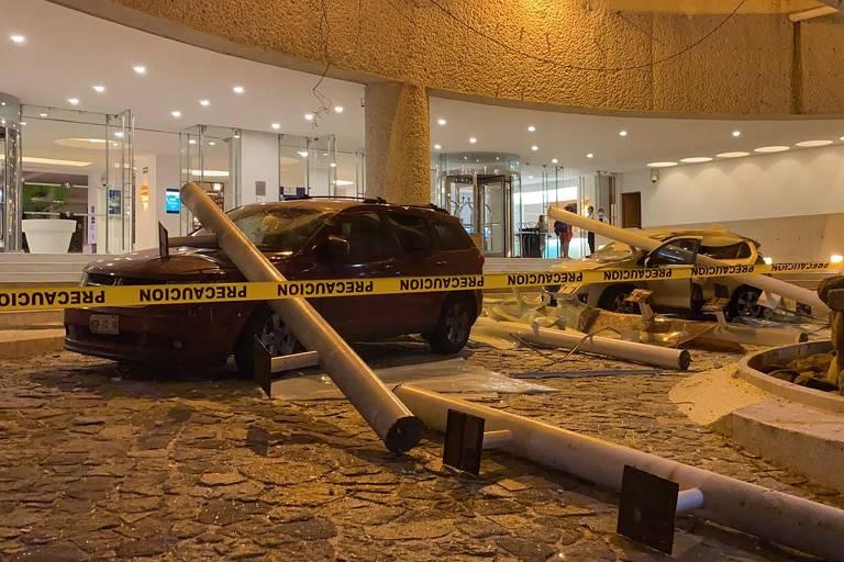 Poste caído sobre carro em meio a outros destroços, em área isolada por fita amarela