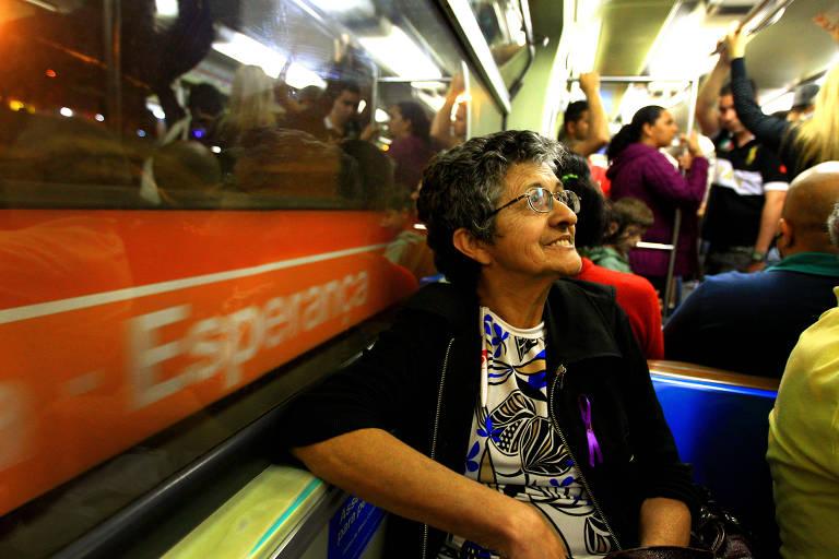 mulher idosa sentada na janela de vagão de metrô em movimento