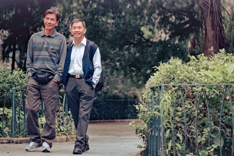 Dois senhores caminham por um parque, com árvores e arbustos ao redor