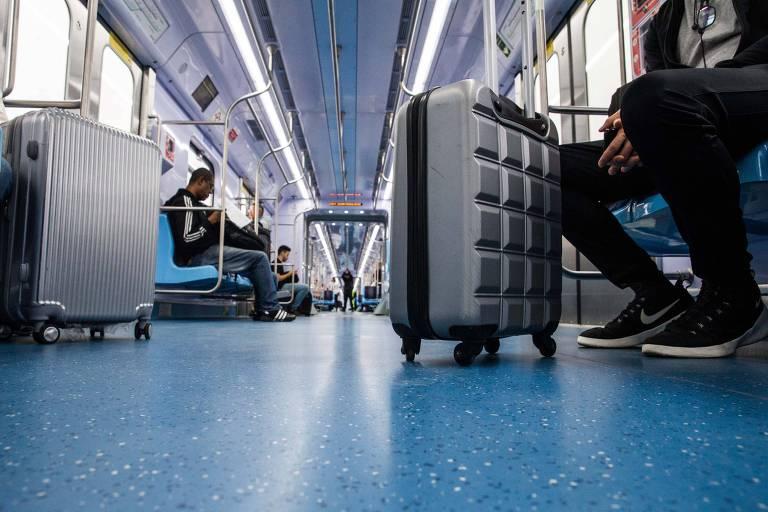 Foto de dentro do trem mostra o vagão quase vazio; em primeiro plano, uma mala em frente a um passageiro