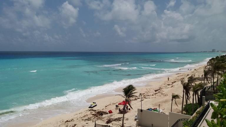 Panorâmica com praia com água muito azul, com céu claro e coqueiros