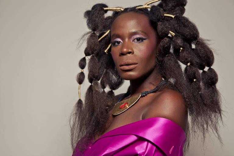 A atriz Isabél Zuaa está com um penteado afro em seus cabelos longos e veste um vestido pink com um colar africano