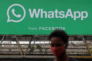 A man walks past a hoarding of the WhatsApp application installed at a skywalk in Mumbai