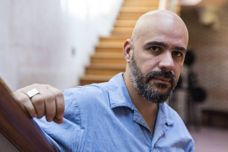 Homem careca e de barba com camisa azul, apoiando a mão direita em uma superfície