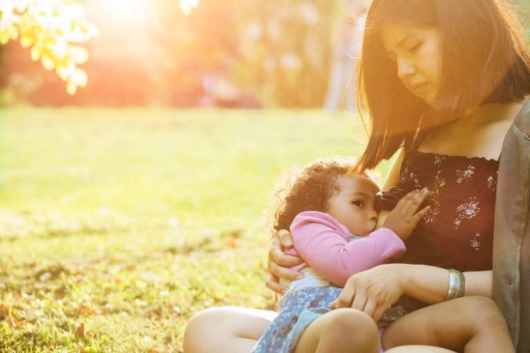 Sentada em um parque uma mãe amamenta uma menina de aproximadamente dois anos. Um forte raio de sol ilumina a cena