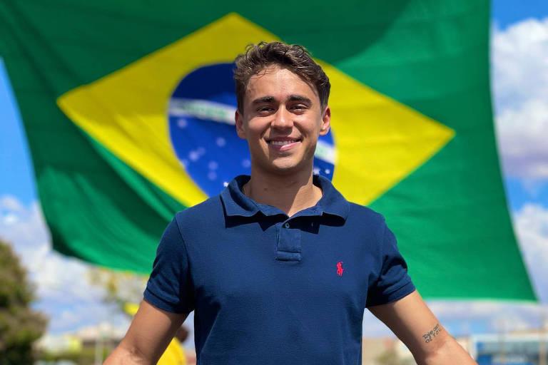 O vereador Nikolas Ferreira na frente de uma bandeira do Brasil