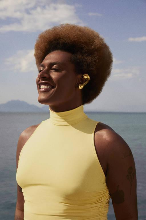 Mulher trans negra usa blusa amarela e sorri