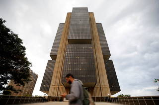 FILE PHOTO: A man walks in front of the central bank headquarters building in Brasilia