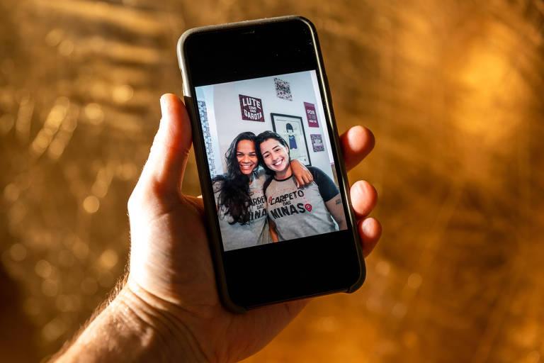 Duas mulheres são vistas em um retrato mostrado na tela de um celular segurado por uma mão