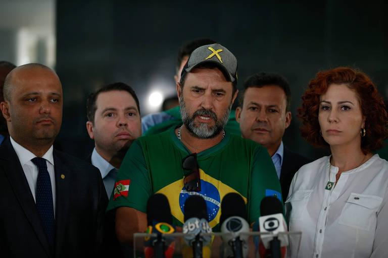 Ao lado de deputados bolsonaristas como Major Vítor Hugo (esq.) e Carla Zambelli (dir.), o líder de manifestantes Chicão Caminhoneiro fala após a conversa que teve com Bolsonaro no Planalto