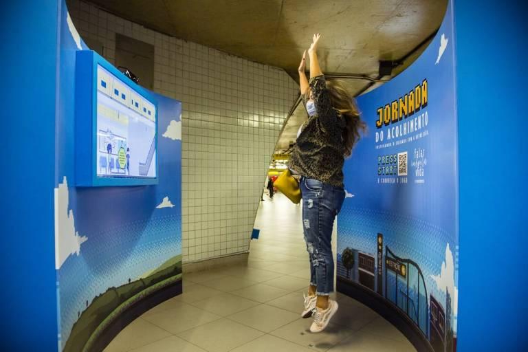 Passageira do metrô brinca com o game da campanha Jornada do Acolhimento, na estação Paulista
