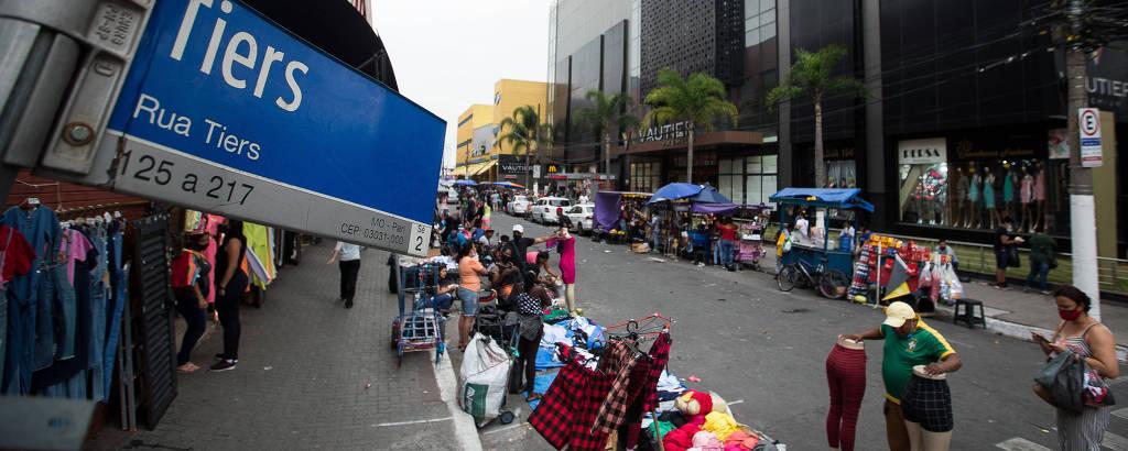Visão panorâmica da rua Tiers, no Brás, que mostra a calçada tomada por vendedores ambulantes e suas mercadorias espalhadas pela calçada