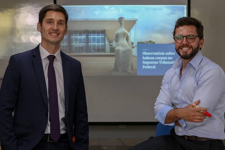 Dois homens brancos sorrindo diante de uma projeção onde se vê a sede do STF e a estátua da Justiça