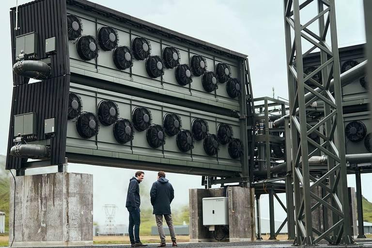 Dois homens conversam diante de uma grande estrutura de concreto e metal usada para capturar dióxido de carbono da atmosfera