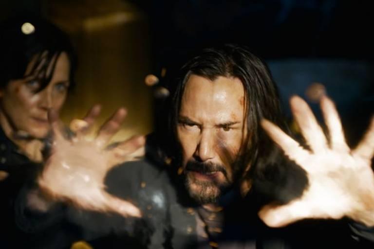 Keanu Reeves interpretando seu personagem Neo ao lado de Trinity de Carrie-Anne Moss (à esquerda)