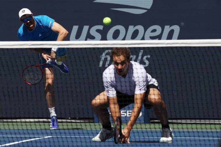 Soares agachado em frente à rede, enquanto Murray saca ao fundo