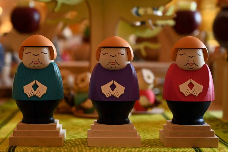 Três bonequinhos de madeira em forma de mulher gordinha, com cabelos loiros e mãos em frente ao ventre em forma de losango. Cada um tem uma roupa de cor diferente: turquesa, roxo e rosa