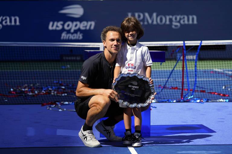 Bruno agachado ao lado de Noah em frente à rede; o menino segura a bandeja do vice-campeão
