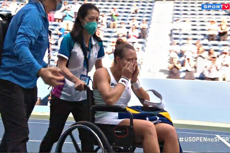 Luisa enxuga lágrimas enquanto é empurrada na cadeira para fora da quadra