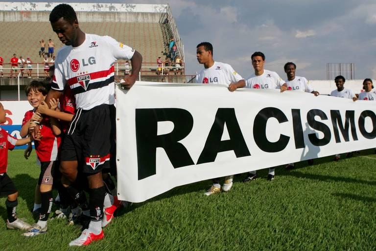 """Jogadores do São Paulo, liderados pelo atacante Grafite, entram em campo com faixa contra o racismo. Grafite está com cabeça abaixada e com o uniforme branco do São Paulo. A faixa que ele segura à frente é branca e tem o dizer """"Racismo"""" em preto"""
