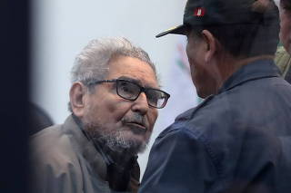 FILE PHOTO: Shining Path founder Abimael Guzman attends a trial during sentence of a 1992 Shining Path car bomb case in Miraflores, at a high security naval prison in Callao