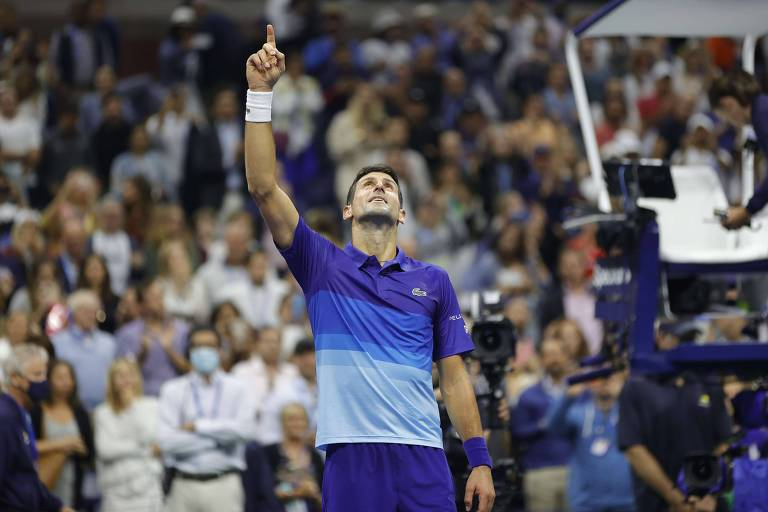 Djokovic, de camiseta e shorts azuis, aponta e olha para o alto em quadra