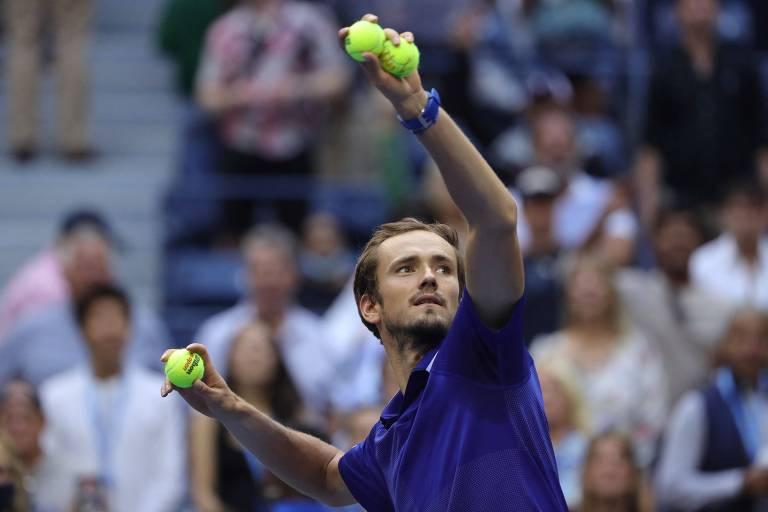 Medvedev, de camiseta azul, arremessa bolas de tênis para o público
