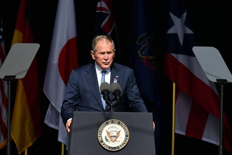 Homem fala em pequeno palanque com bandeiras dos Estados Unidos ao fundo