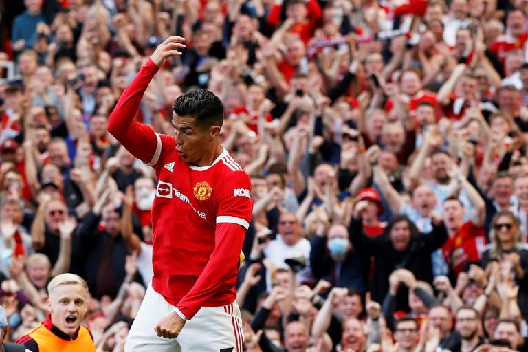Cristiano Ronaldo, de vermelho, salta para comemorar seu primeiro gol no retorno ao Manchester United enquanto a torcida vibra ao fundo.