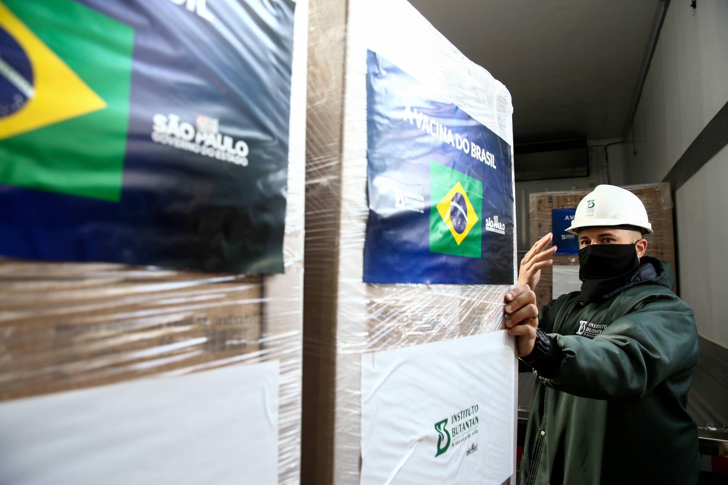 Funcionário do Butantan embarca caixas com a Coronavac em caminhão de distribuição