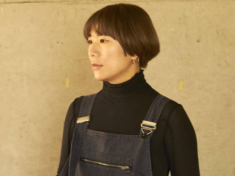 mulher japonesa de cabelos curtos diante de parede amarela