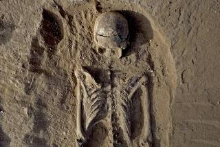 Handout photo shows the skeleton of a man, found lying prone in the sediments of a lagoon 30km west of Lake Turkana, Kenya, at a place called Nataruk
