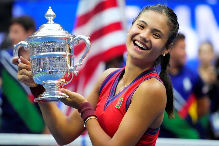 Tenista vestida com roupa vermelha sorri segurando o troféu