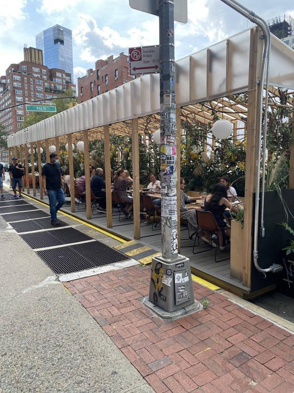 Vista geral da calçada e das mesinhas do lado de fora do restaurante em Nova York