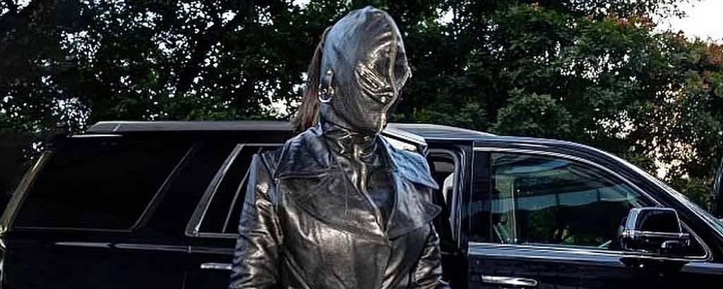 Mulher se veste inteira de couro, com luvas, botas e uma máscara que cobre todo o rosto, a única parte visível é o rabo de cabelo, que sai da parte de trás da máscara