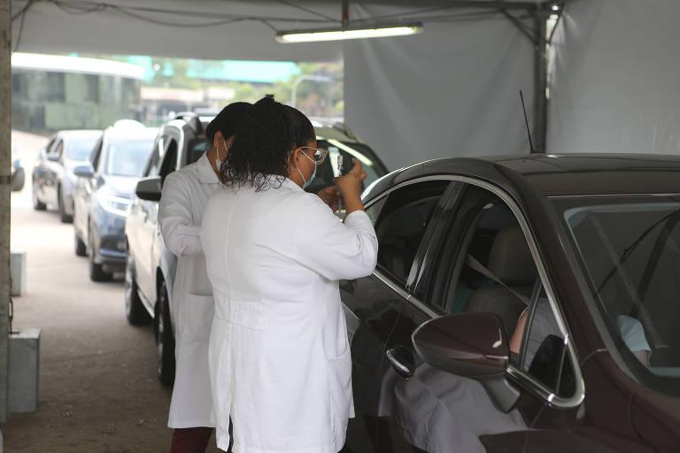 Imagem mostra equipe de enfermagem ao lado de veículo, para vacinar adolescente contra a Covid-19