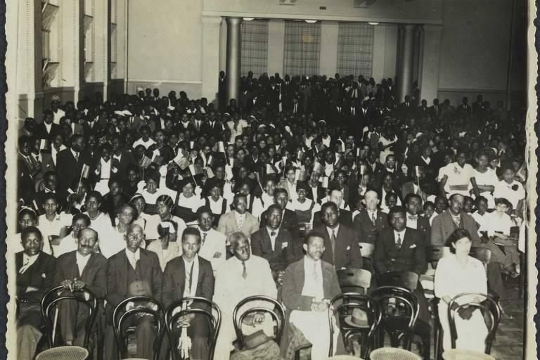 um grupo de pessoas, homens e mulheres, está sentado em um salão