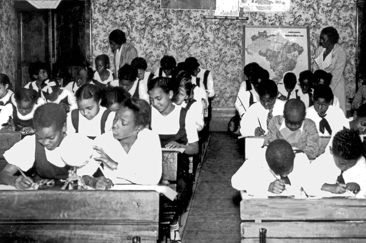 Em uma sala de aula, um grupo de crianças estão sentadas em carteiras escolares