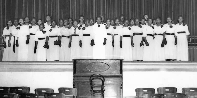 Imagem em preto e branco mostra um grupo de mulheres em um palco