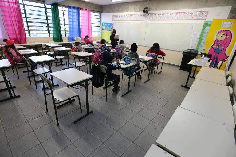 sala de aula com carteiras cinza. poucas crianças ocupam o local, usando máscara