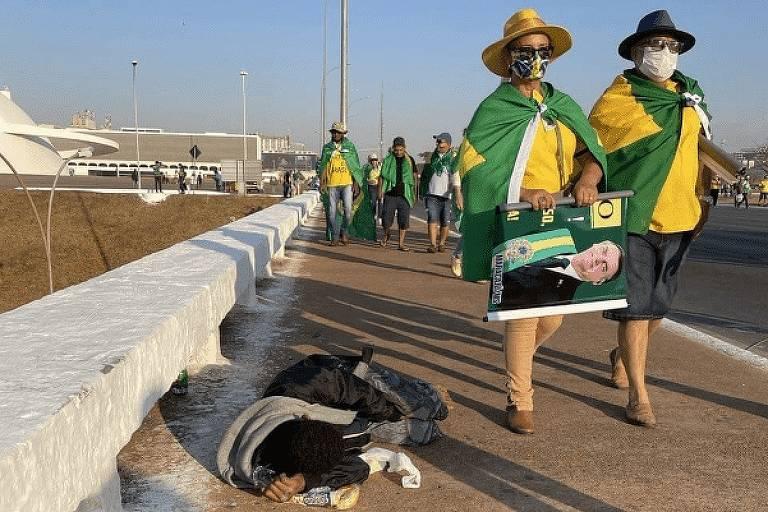 Duas pessoas vestidas de verde amarelo e com a bandeira do Brasil caminham ao lado de pessoa deitada no chão