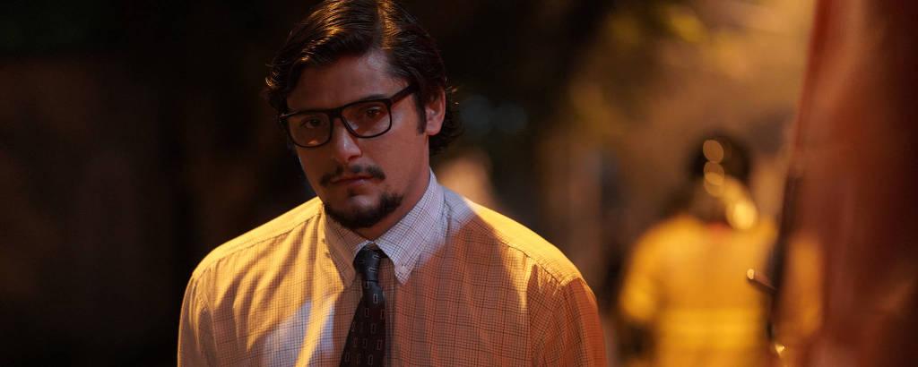 Homem branco usando óculos de armação preta, camisa social branca quadriculada e gravata marrom