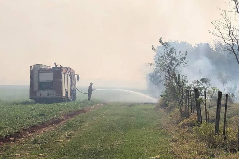 Bombeiros trabalham para acabar com incêndio causado por queda de avião da FAB, em Campo Grande